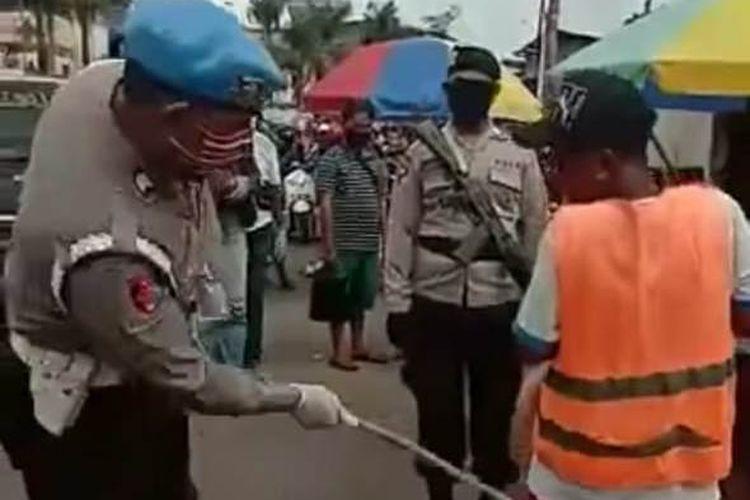 Sejumlah anggota Polda Maluku menggelar razia penertiban warga yang tidak mengenakan masker di kawasan Pasar Mardika Ambon, Kamis (28/5/2020). Tampak bokong warga warga yang tidak mengenakan masker dipukuli anggota polisi dengan rotan.