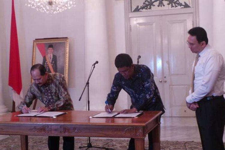 Gubernur DKI Jakarta Basuki Tjahaja Purnama bersama Dirut PT PAM Jaya Erlan Hidayat (pakai batik cokelat) dan Dirut PD PAL Jaya Juniver Pandjaitan (pakai batik biru), saat penandatanganan nota kesepahaman penggabungan PT PAM Jaya dengan PD PAL Jaya, di Balai Kota, Rabu (23/12/2015).