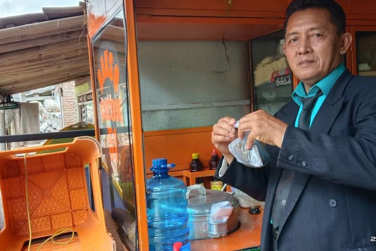 Agus Mujianto menggunakan jas, dasi dan sepati pantofel saat hendak menjual ciloknya di pasar Jenggawah Jember