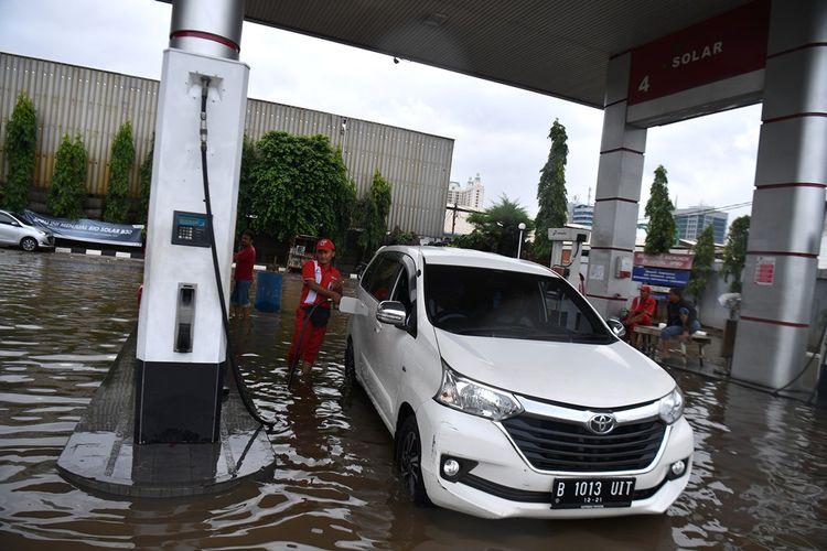 Karyawan melayani pengisian bahan bakar minyak (BBM) saat banjir menggenangi SPBU Pertamina di Jalan Danau Sunter Selatan, Sunter Jaya, Jakarta Utara, Minggu (23/2/2020). Hujan deras sejak Minggu 23 Februari dini hari membuat sejumlah daerah di Ibu Kota tergenang banjir.