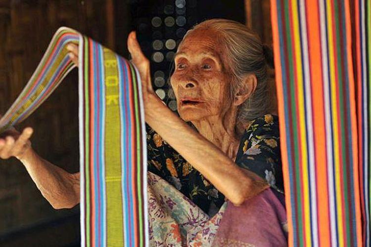 Inaq Melan (60), menjajakan kain tenun di Desa Sade, Kecamatan Pujut, Kabupaten Lombok Tengah, Nusa Tenggara Barat.