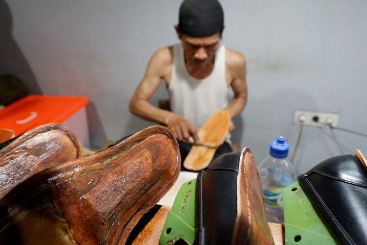 Seorang perajin tengah mengerjakan sepatu Minen, merk sepatu di Bandung yang sudah tembus pasar dunia.