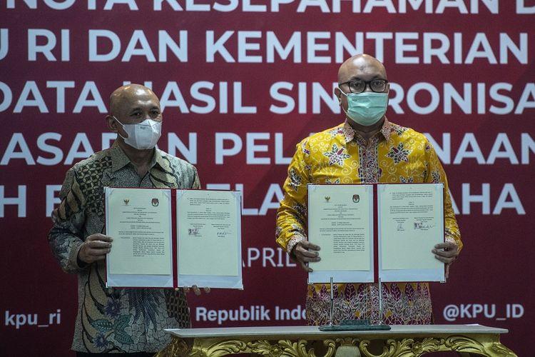 Ketua KPU Ilham Saputra (kanan) bersama Menteri Koperasi dan UKM Teten Masduki menunjukan dokumen nota kesepahaman tentang dukungan Pemulihan Ekonomi Nasional (PEN) usai penandatanganan di Kantor KPU, Jakarta, Kamis (29/4/2021). Ruang lingkup kerja sama tersebut meliputi penyusunan standar operasional prosedur (SOP) pemanfaatan, pengelolaan dan penggunaan data pemilih berusia paling rendah 18 tahun sebagai salah satu dasar verifikasi pendataan sasaran pelaksaan Bantuan Pemerintah bagi Pelaku Usaha Mikro (BPUM) dalam rangka meningkatkan jumlah penerima BPUM. ANTARA FOTO/Aprillio Akbar/wsj.