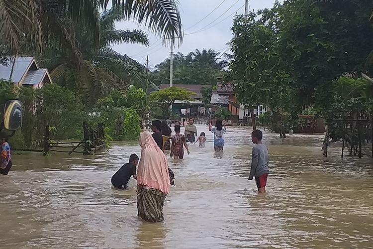 Sejumlah warga melintasi jalan yang digenangi banjir di Desa Sahilan Darussalam, Kecamatan Gunung Sahilan, Kabupaten Kampar, Riau, Kamis (12/12/2019).
