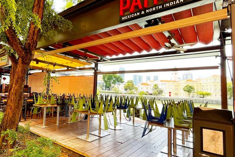 Kursi-kursi di Restoran Patro yang menjual makanan India Utara dan Meksiko di kawasan Boat Quay, Singapura terlihat dilipat. Salah satu kebijakan utama lockdown parsial Singapura adalah melarang warga mengonsumsi makanan di pusat-pusat makanan seperti restoran, food court, hawker, dan kedai kopi mulai 16 Mei hingga 13 Juni 2021. Larangan ini juga diterapkan pada lockdown parsial atau circuit breaker Singapura tahun 2020 lalu.