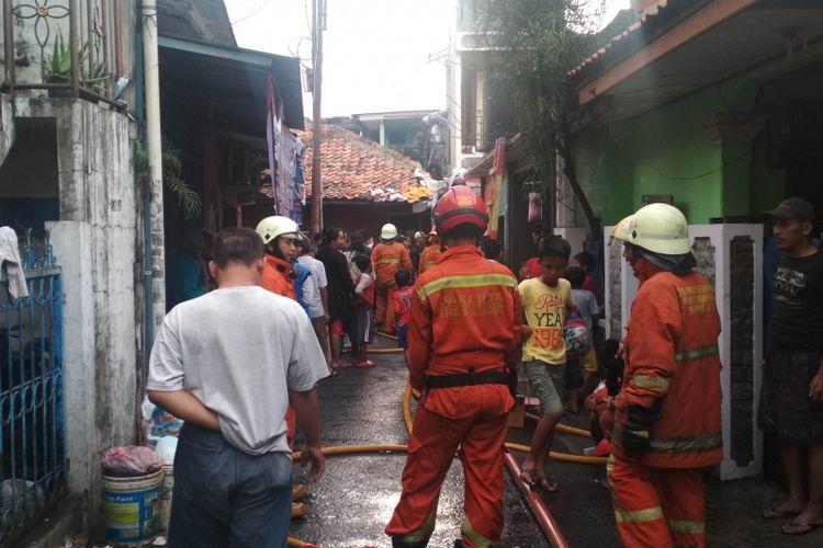 Petugas pemadam kebakaran memadamkan api yang menghangsukan lima rumah warga di Pondok Indah, Jakarta Selatan, Senin (28/1/2019)