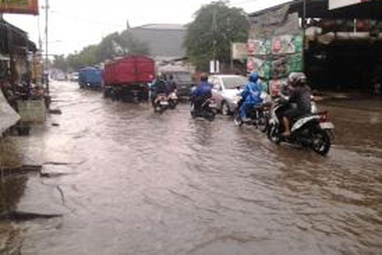 Hujan deras yang mengguyur kota Tangerang Selatan dan menutup jalan berlubang sangat mebahayakan pengguna jalan, Senin (14/4/2014).