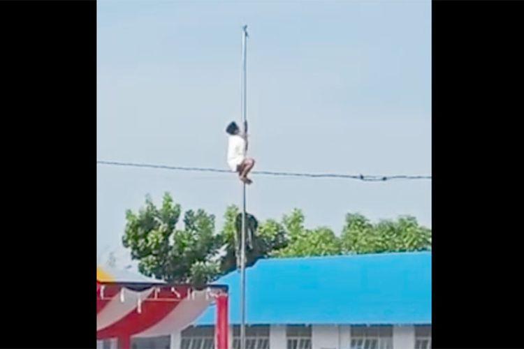Didin, santri Pesantren Alislam di Kabupaten Gorontalo memanjat tiang saat bendera merah putih siap dikibarkan namun tiba-tiba tali putus. Ia memanjat hingga ke puncak tiang meskipun kain sarung yang dikenakan terlepas.