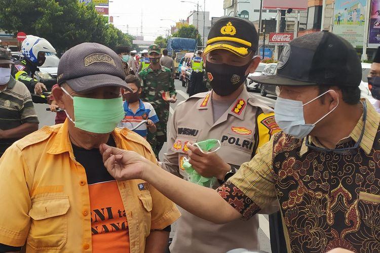 Kapolresta Banyumas Kombes Whisnu Caraka bersama Bupati Banyumas Achmad Husein membagikan masker kepada masyarakat di sekitar Alun-alun Purwokerto, Kabupaten Banyumas, Jawa Tengah, Kamis (10/9/2020).