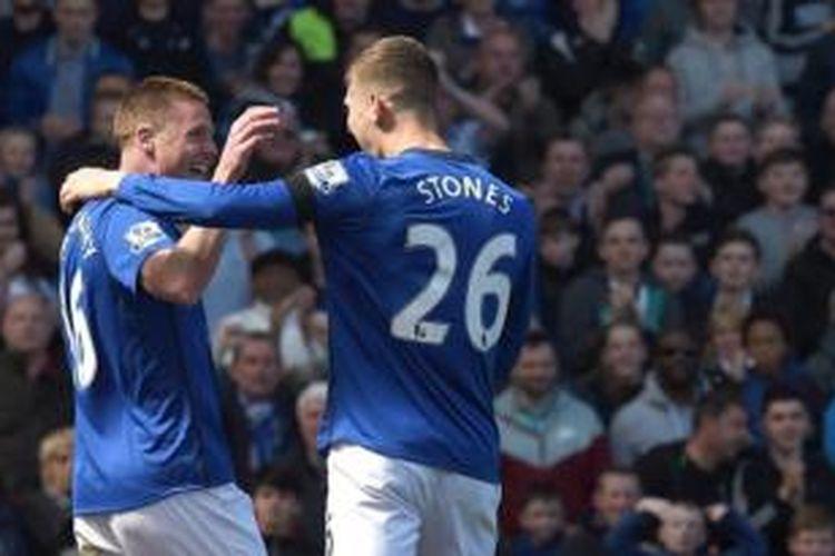 Bek Everton, John Stones (kanan), merayakan gol ke gawang Manchester United pada laga Premier League di Stadion Goodison Park, Liverpool, Minggu (26/4/2015).