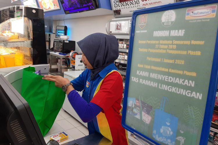 Petugas kasir Indomart Jalan Peleburan No.2 Semarang Selatan melayani pembeli dengan tas ramah lingkungan, Jumat (03/01/2020)