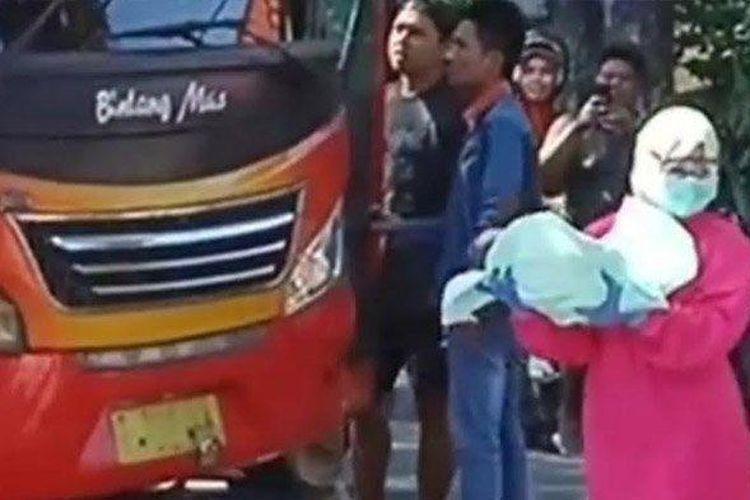 Petugas medis membopong bayi dari penumpang perempuan asal Tuban yang melahirkan di bus tujuan Surabaya, Selasa.