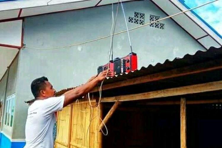 Foto : Seorang guru di SMPN Pruda, Desa Puda, Kecamatan Waiblama, Kabupaten Sikka, menyimpan radio di atas atap sekolah.