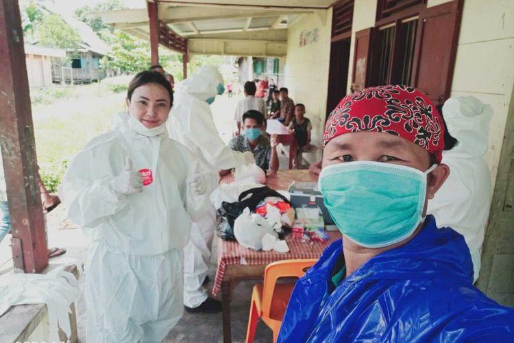 Dengan menggunakan jas hujan warna biru dan penutup kepala, Onlihu Ndraha, Warga Desa Desa Tagaule, Kecamatan Bawolato, Kabupaten Nias, Sumatera Utara, saat bersama Tim Kesehatan Kabupaten Nias, melakukan rapid tes bagi 8 warga yang mengalami demam.