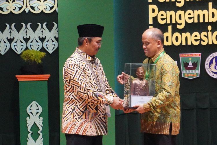 Ketua ICMI Jimly Asshidiqie (kiri) menyerahkan ICMI Award kepada anak BJ Habibie, Ilham Habibie, Jumat (6/12/2019) di auditorium UNP