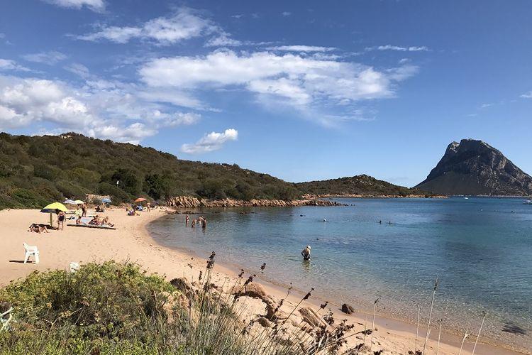 Para wisatawan sedang menikmati pantai Porto San Paolo di pesisir timur Pulau Sardinia, Italia.
