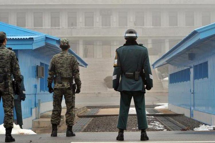 Tentara Korea Selatan berjaga di desa Panmunjom, zona demiliterisasi yang memisahkan kedua Korea. Secara teknis Korea Utara dan Selatan masih dalam kondisi perang karena Perang Korea 1950-1953 berhenti karena perjanjian gencatan senjata, bukan perjanjian damai.