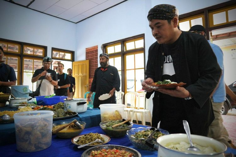 Wakil Bupati Jombang, Sumrambah (kanan), bersama Ketua Kampung Adat Segunung, Giri Winarko (kiri), saat mencoba menu kuliner khas pedesaan yang disiapkan di Kampung Adat Segunung, Wonosalam, Kabupaten Jombang, Jawa Timur, Sabtu (7/3/2020).