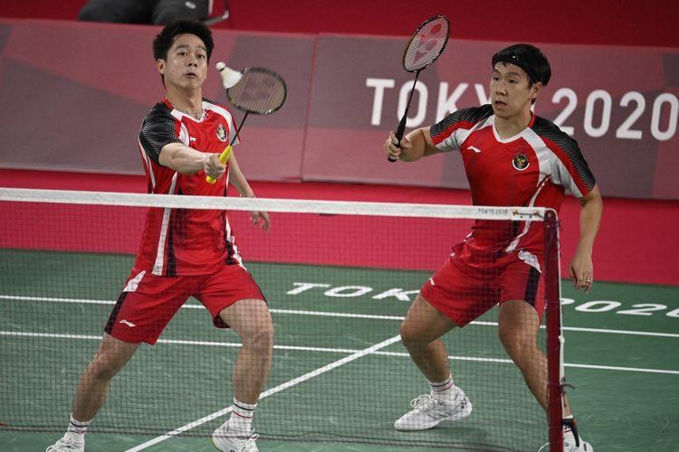 Pasangan ganda putra Indonesia Kevin Sanjaya Sukamuljo  (kiri) dan Marcus Fernaldi Gideon bermain lawan wakil Britania Raya Sean Vendy dan Ben Lane di laga fase grup Olimpiade Tokyo 2020, Sabtu (24/7/2021).