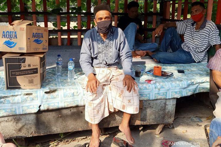 Ketua RT015 RW07 Jati, Suraji (65), berpose di depan kediamannya kawasan Jati, Kecamatan Pulo Gadung, Jakarta Timur, Rabu (1/7/2020), usai memberikan klarifikasi terkait dugaan pungutan liar terhadap distribusi bantuan sosial COVID-19 dari pemerintah provinsi setempat.