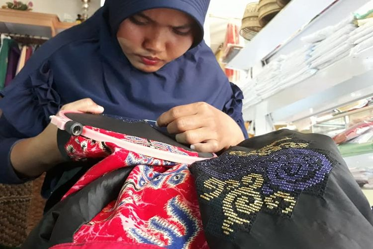 Seorang wanita di sela kesibukannya sebagai ibu rumah tangga membuat sulaman karawo. Karawo merupakan sulamaan yang sangat rumit, dibuat dengan cara mencabut serat kain sesuai pola, menyulam dengan benang dan mengikatnya.