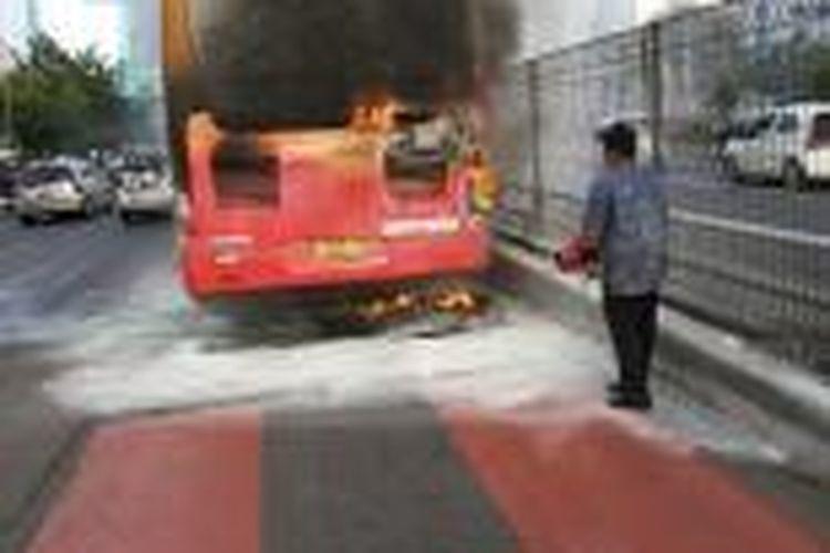 Sopir Transjakarta berupaya memadamkan api yang membakar bus jenis Zhongthong tak jauh dari halte Pancoran Barat, Minggu (8/3/2015).
