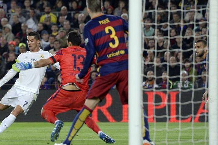 Penyerang Real Madrid, Cristiano Ronaldo (kiri), melepaskan tembakan yang tak mampu dihalau kiper Barcelona asal Cile, Claudio Bravo, untuk mencetak gol dan membawa Madrid menang 2-1 pada el clasico dalam lanjutan La Liga di Camp Nou, Sabtu (2/4/2016).