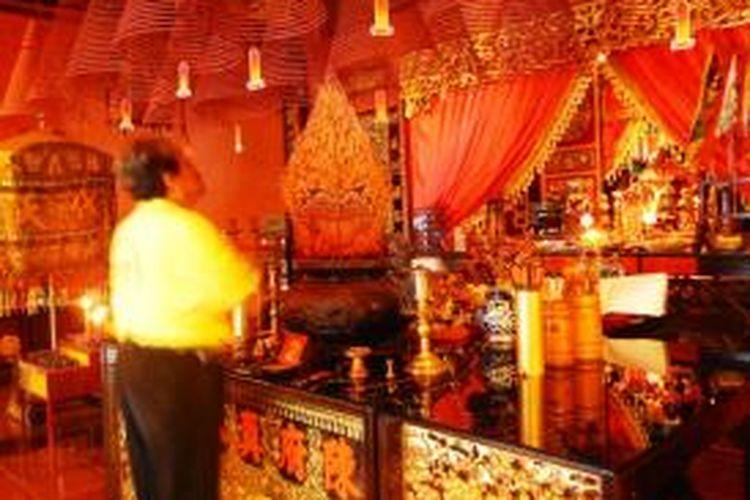 Pengurus kelenteng Hoo Tong Bio Banyuwangi saat melakukan sembayangan meletakkan gunungan wayang di atas altar.