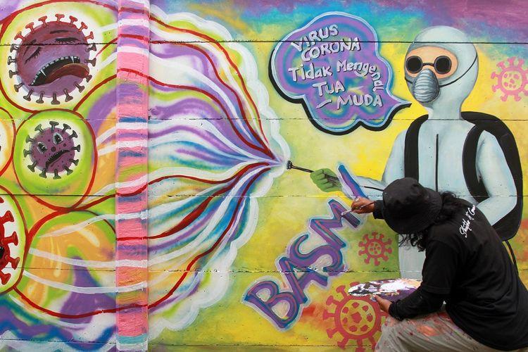 Seorang seniman mural membuat mural dengan tema kampanye melawan COVID -19 di kawasan Tanah Tinggi, Tangerang, Banten, Rabu (20/1/2021). Kampanye dalam bentuk mural melawan COVID-19 tersebut merupakan bagian dari edukasi bagi masyarakat untuk lebih meningkatkan kewaspadaan terhadap pandemi itu. ANTARA FOTO/Muhammad Iqbal/foc.