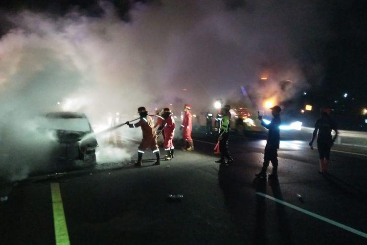 Petugas memadamkan api yang membakar Toyota Avanza di Tol Bawen.