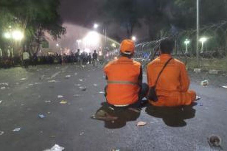 Dua petugas kebersihan dari Dinas Kebersihan DKI Jakarta terlihat sedang menyaksikan proses pembubaran paksa yang dilakukan polisi terhadap massa buruh dalam aksi unjuk rasa di seberang Istana Merdeka, Jakarta, Jumat (30/10/2015) malam.