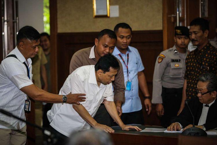 Tersangka kasus korupsi proyek e-KTP, Setya Novanto berbicara dengan penasehat hukumnya pada sidang perdana di Gedung Pengadilan Tipikor, Jakarta, Rabu (13/12/2017). Setya Novanto akan menghadapi sidang pembacaan dakwaan oleh jaksa penuntut umum.