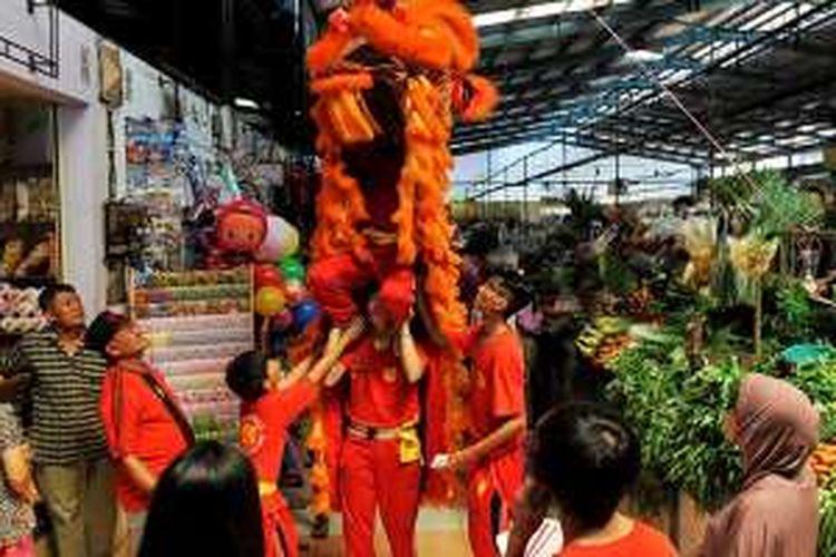 Pemain barongsai mengambil angpau yang disediakan pedagang di depan lapak mereka di Pasar Modern BSD City, Tangerang Selatan, Sabtu (6/2/2016). Barongsai yang berkeliling pasar untuk mengambil angpau tersebut merupakan tradisi menjelang perayaan Imlek.