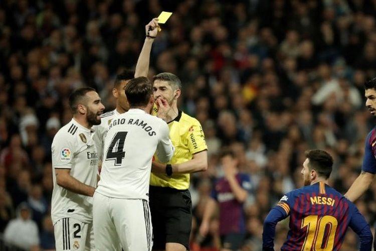 Wasit Alejandro Hernandez memberikan kartu kuning kepada Sergio Ramos dalam laga Real Madrid vs Barcelona dalam lanjutan pekan ke-26 Liga Spanyol 2018-2019 yang digelar di Stadion Santiago Bernabeu, 2 Maret 2019.