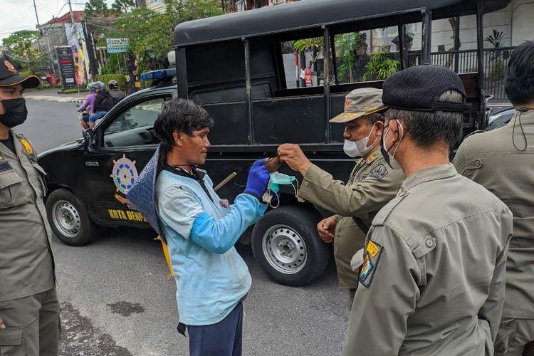 Petugas Satpol PP Kota Denpasar saat memberikan masker medis kepada Nengah Budiasa setalah sebelumnya menggunakan masker yang terbuat dari batok kelapa