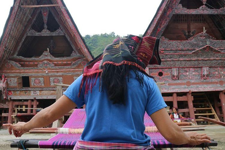 Pengrajin kain ulos sedang menenun di depan rumahnya di desa Meat
