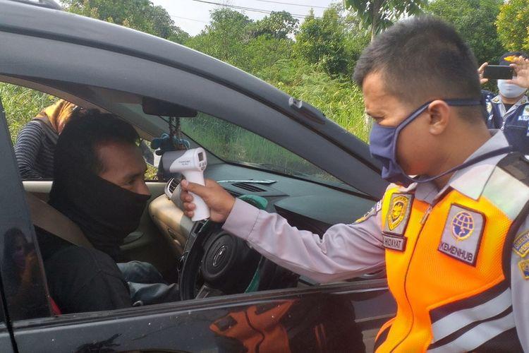 Pemeriksaan suhu tubuh pengendara yang hendak masuk ke Kota Pekanbaru di perbatasan Pekanbaru-Kampar, dalam masa PSBB untuk mencegah penyebaran Covid-19, Minggu (19/4/2020).