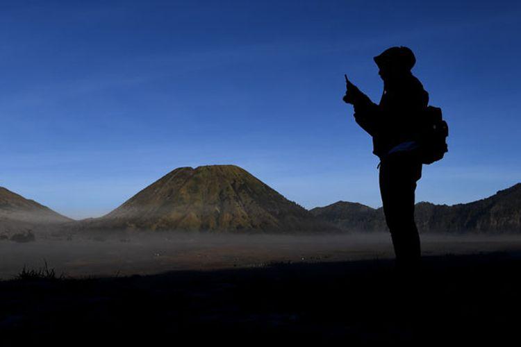 Pengunjung mengambil gambar hamparan pasir yang diselimuti empun upas dengan gawai miliknya di kawasan Gunung Bromo, Probolinggo, Jawa Timur, Minggu (30/6/2019). Fenomena embun upas tersebut disebabkan penurunan suhu yang mencapai 0 derajat celcius pada malam hari.