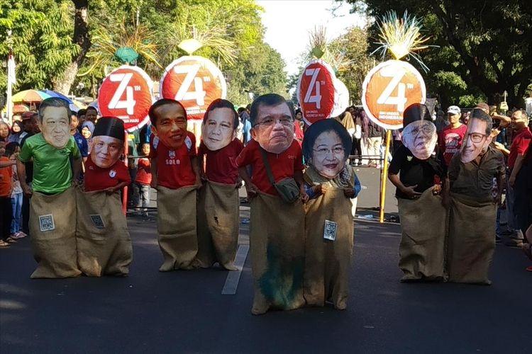 Lomba balap karung warga memakai topeng tokoh nasional untuk memerihakan HUT ke-74 RI di CFD Jalan Slamet Riyadi Solo, Jawa Tengah, Minggu (4/8/2019).