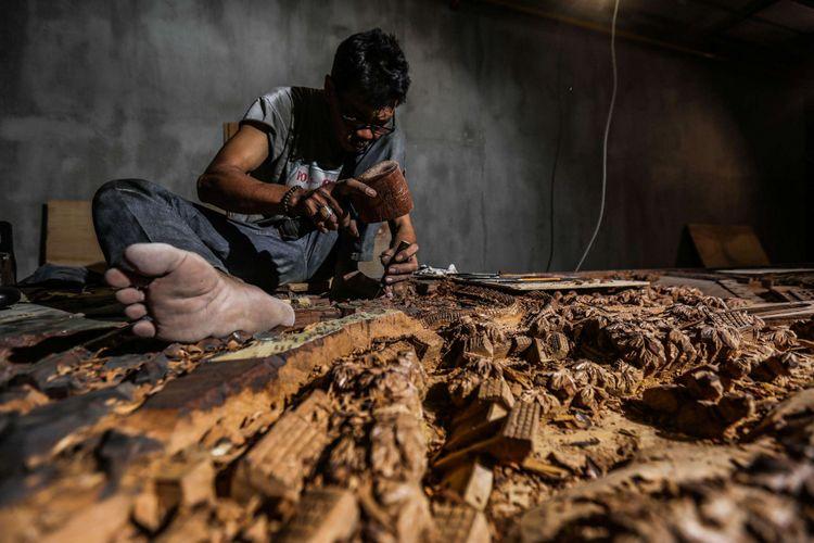 Yatiman seniman seni ukir relief 3 dimensi asal Jepara saat menyelesaikan hasil karyanya di Tangerang, Banten, Rabu (17/01/2017). Yatiman menjadi seorang seniman ukir kayu sejak umur 19 tahun di Jepara Jawa Tengah.