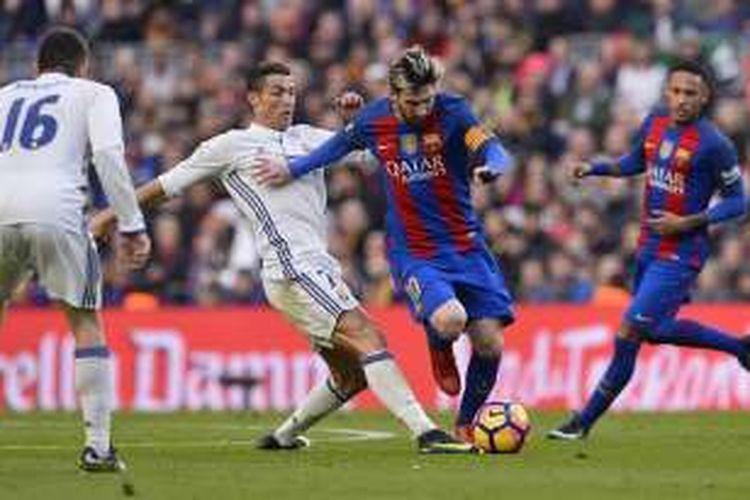 Pemain FC Barcelona, Lionel Messi, sedang dibayang-bayangi oleh pemain Real Madrid, Cristiano Ronaldo, dalam laga La Liga di Stadion Camp Nou, 3 Desember 2016.