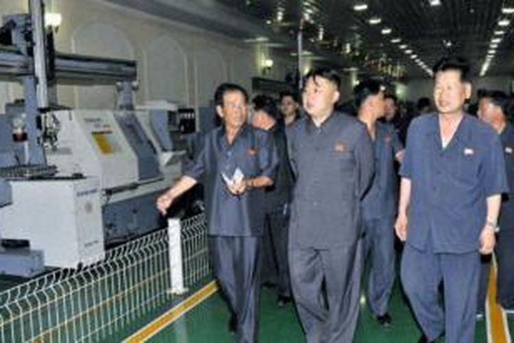 Dalam foto ini terlihat Pemimpin Korea Utara Kim Jong Un meninjau sebuah pabrik di Pyongyang. Korea Utara mengklaim telah mampu memproduksi telepon pintar dengan nama Arirang.