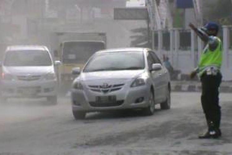 Petugas mengatur lalu lintas di saat hujan abu di bundaran Kartasura, Senin (18/11/2013).