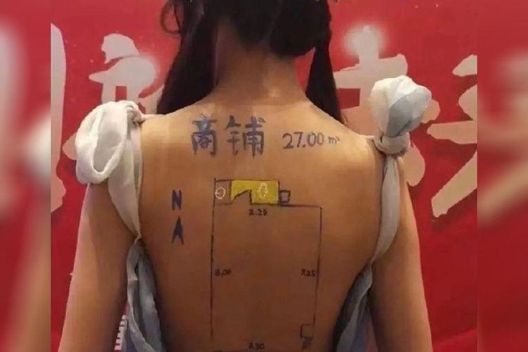 Agen perumahan China berjualan di pameran dengan menggambar denah lantai di punggung wanita, pada Selasa (23/3/2021).