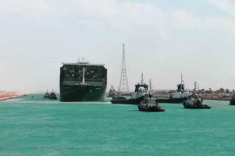 Dalam foto yang dirilis Otoritas Terusan Suez, Ever Given, sebuah kapal kargo berbendera Panama ditemani kapal tunda Terusan Suez berlayar di Terusan Suez, Mesir, Senin (29/3/2021). Tim penyelamat pada Senin membebaskan kapal kontainer tersebut yang telah menghentikan perdagangan global melalui Terusan Suez, mengakhiri krisis yang selama hampir sepekan telah menyumbat salah satu arteri maritim paling vital di dunia.