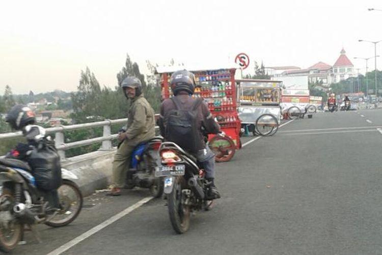 Flyover Pasar Rebo, Ciracas, Jakarta Timur atau terkenal dengan jembatan cinta menjadi lokasi pedagang kaki lima, pengendara, serta muda-mudi nongkrong dan pacaran di pinggir jalan. Foto ini diambil pada Kamis (11/9/2014) sekitar pukul 16.30 WIB.