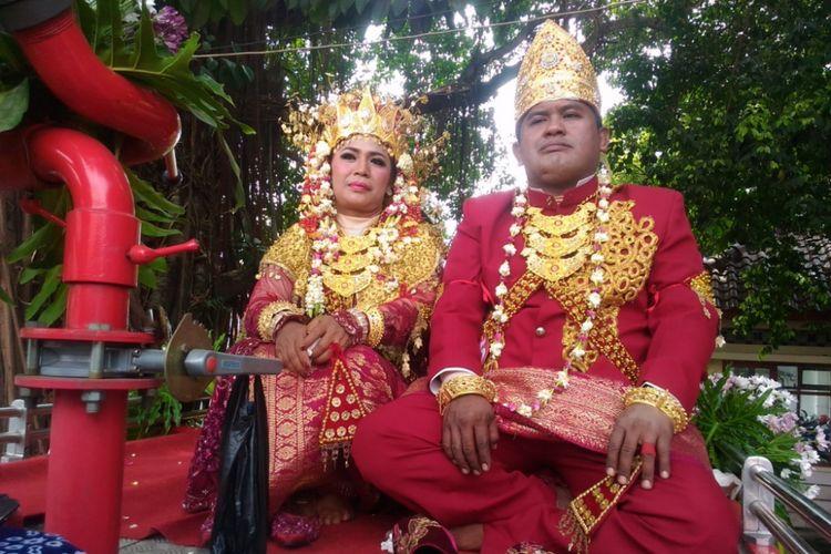 Sudibyo (40) dan Warsini Haryati (43) ketika mengikuti nikah massal di atas mobil pemadam kebakaran di pintu keluar DPRD DI Yogyakarta, Jalan Malioboro, Kota Yogyakarta, Selasa (26/9/2017)