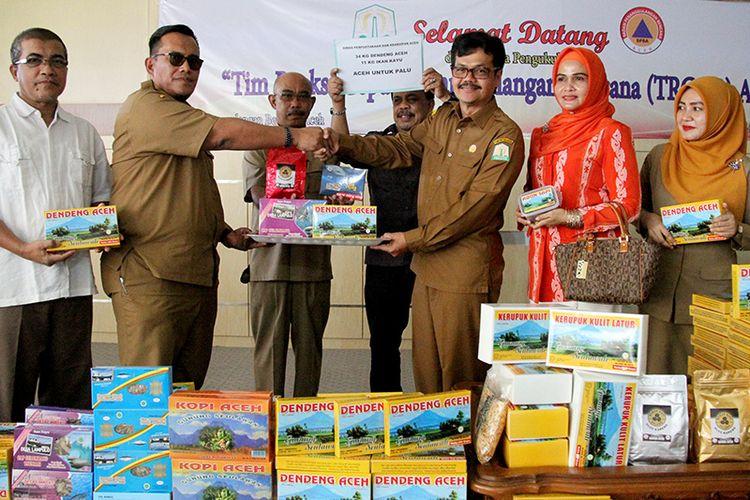 Teuku Ahmad Dadek, Kepala BPBA menerima sumbangan dendeng dan ikan keumamah dari Kepala Dinas Perpustakaan dan Kearsipan Aceh, Wildan di ruang Aula Kantor BPBA di Banda Aceh,  Selasa (09/10/18).