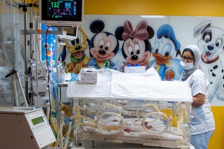 Seorang anggota staf medis mensurvei satu dari sembilan bayi yang disimpan di inkubator, sehari setelah mereka lahir dari seorang wanita Mali di klinik di kota Casablanca, Maroko barat, pada 5 Mei 2021
