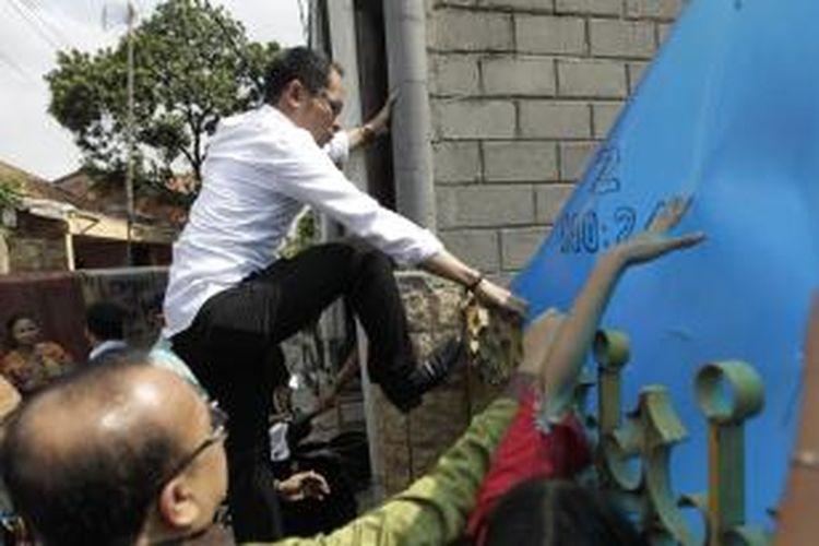 Menteri Ketenagakerjaan Hanif Dhakiri melompati pagar saat melakukan inspeksi mendadak di Perusahaan Pengerah Tenaga Kerja Indonesia Swasta (PPTKIS) Elkari Makmur Sentosa yang terletak di Jalan Asem Baris Raya, Gang Z, Tebet, Jakarta Selatan, Rabu (5/11/2014). Dalam sidak kali ini Menaker menemukan sejumlah pelanggaran di antara lain tempat tidur yang tidak layak dan penampungan yang tertutup. KOMPAS IMAGES/RODERICK ADRIAN MOZES